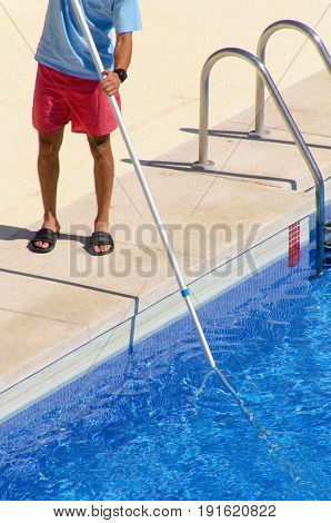 Guy Cleaning The Swimming Pool With A Telescopic Brush