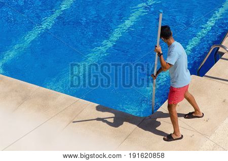 Guy Cleaning The Swimming Pool With A Telescopic Vacuum Head