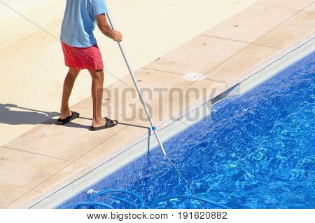 Guy Cleaning The Swimming Pool With A Vacuum Head