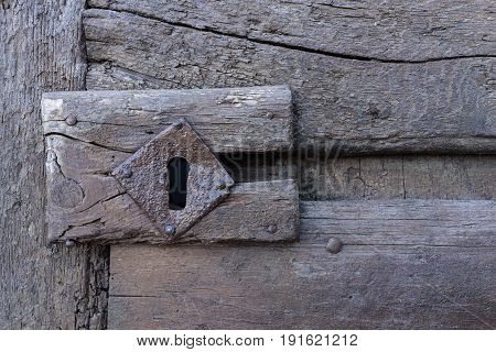 vintage aged wooden door with keyhole in Matera south Italy.