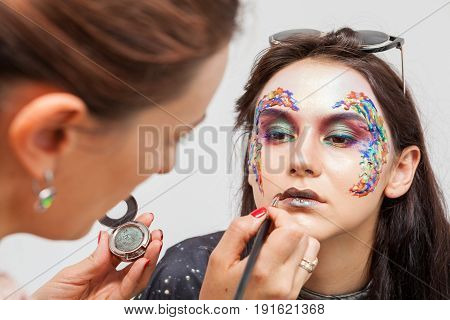 Make-up artist applying lipstick to model. Beauty and fashion. Creativity and makeup. Cosmetics and backstage preparation for photo shooting