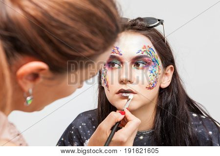 Make-up artist working on a model before photo shooting. Beauty and fashion. Creativity and makeup. Cosmetics and backstage preparation for photo shooting