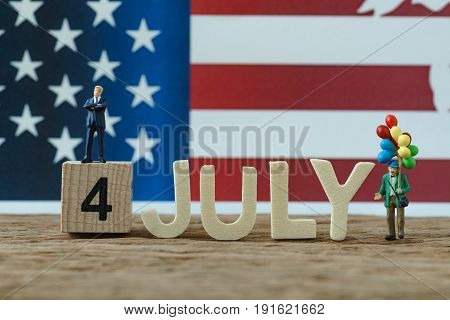 Independence day USA with miniature people old man holding balloon businessman standing on wooden cube number 4 and alphabets JULY and United State national flag in the background.