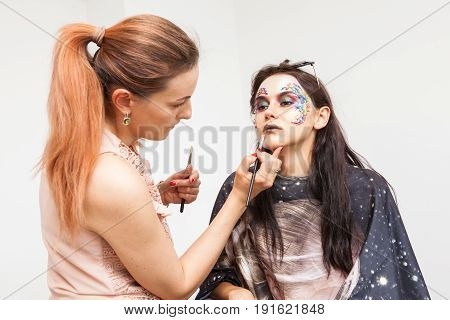 Make-up artist applying creative makeup on beautiful model. Beauty and fashion. Creativity and makeup. Cosmetics and backstage preparation for photo shooting