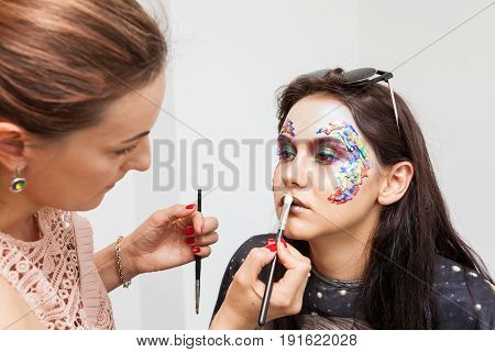 Make-up artist applying artistic makeup on beautiful model. Beauty and fashion. Creativity and makeup. Cosmetics and backstage preparation for photo shooting