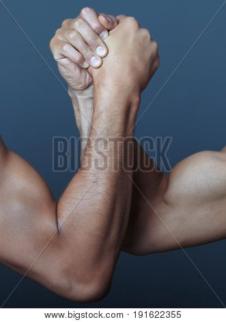 Two hands doing arm wrestling. Vertical photo