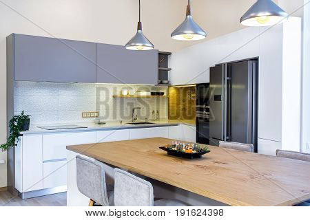 Modern kitchen design in light interior. There is also a kitchen island in the room. Kitchen and living room combined. Float Pendant Light above the kitchen island.