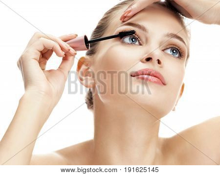 Charming woman applying black mascara on eyelashes. Photo of young woman of European appearance on white background. Beauty concept