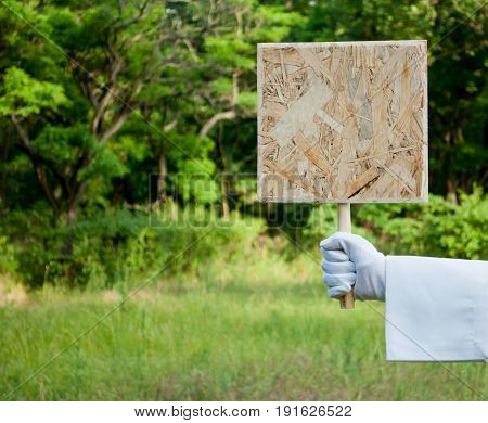 The waiter's hand in a white glove and with a white napkin holds a wooden square tablet or placard on a blurred background of green bushes and grass
