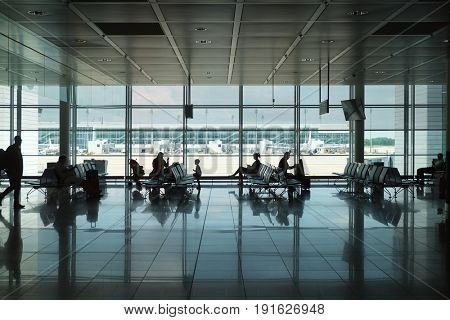 Interior of modern airport with silhouettes of passengers awaiting flight