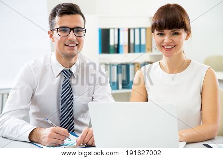 Young business people are looking at the camera smiling at the office