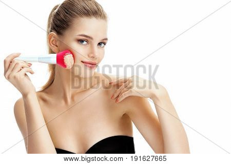 Gorgeous young woman with pink make up brush on her face. Photo of blonde woman on white background. Beauty concept