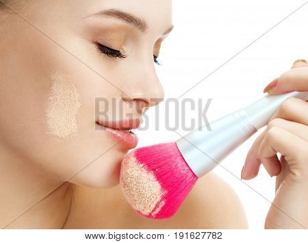 Sensual woman applying dry cosmetic tonal foundation on the face using makeup pink brush. Close up of female profile on white background. Beauty concept