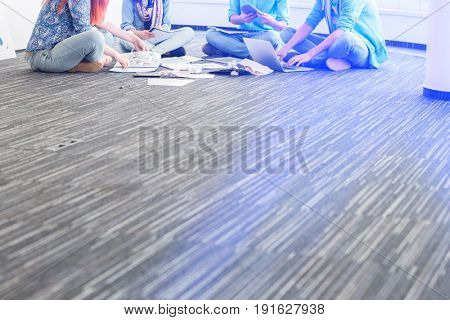 Low section of businesspeople working on floor in creative office