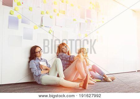 Tired businesswomen sitting on floor in creative office