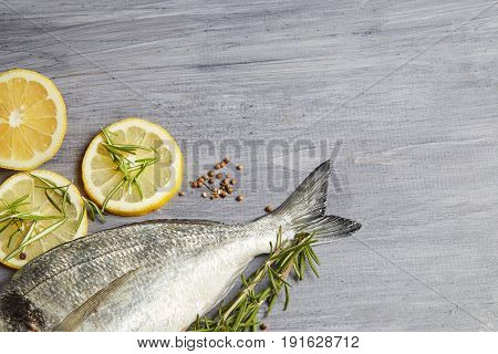 Fresh raw Dorado fish with rosemary garlic tomatoes pepper and lemon on a board. Selective focus. View from above.