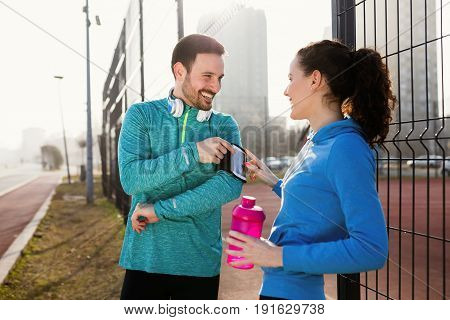 Handsome sportsman listening to music and using smart apps while working out and exercising outdoor