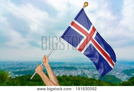 Young man's hands proudly waving the Iceland national flag in the sky, part 3D rendering