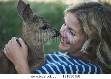 Cute blonde woman playing with roe deer fawn.