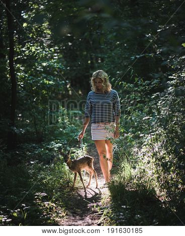 Young beautiful woman walking with roe deer fawn in forest at sunset.