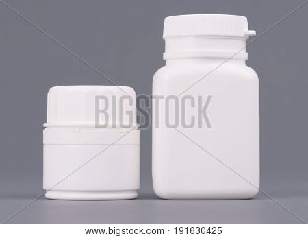 Blank big and medium size medicine white plastic packaging bottles for cosmetics, vitamins, pills or capsules.