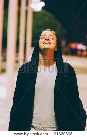 Young handsome happy man in hood outdoors. Portrait of hooded guy walking through night city