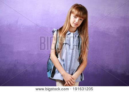 Pretty little girl with schoolbag on color background