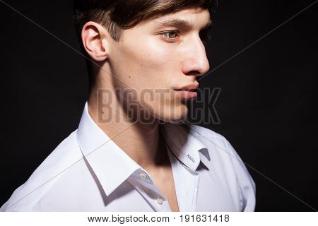 Male model in white shirt on black background in studio photo. Style and fashion. Cool attractive guy