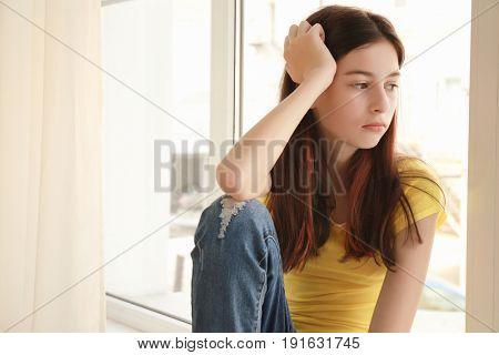 Sad pretty girl sitting on window sill at home