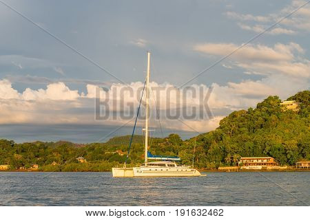 Hell-Ville Madagascar - December 19 2015: Catamaran Dragonfly Fiji in the rays of the setting sun anchored at Andavakotakona Bay near Hell-Ville Nosy Be Island Madagascar.