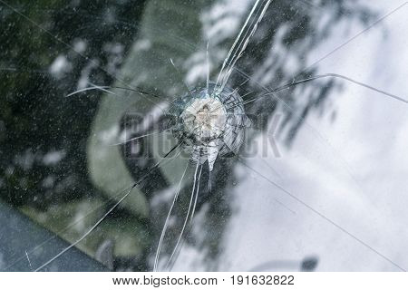 Broken car windshield with radial cracks and a hole in the middle. Glass is dirty with stains after rain. A tree reflected in the glass. Through the window you can see the steering wheel and seat.