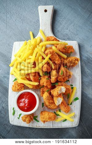 Fried crispy chicken nuggets with french fries and ketchup on white board.