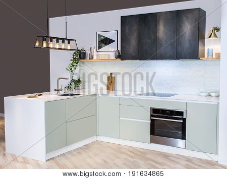 Modern home interior. Front view of modern kitchen design in a light interior. Facades are painted and made of natural stone. European furniture, design, technologies.
