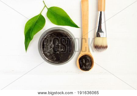 Black clay mineral facial mask in jar with spoon and cosmetic brush, above view white wooden background.