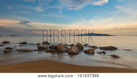 Looking out over the south china sea in Nha Trang bay just after sunset with a colourful cloudy sky a sandy beach and rocks in the foreground.