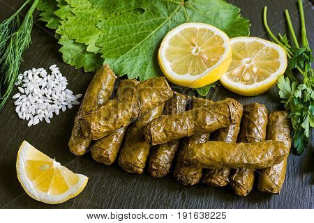 Delicious stuffed grape leaves (the traditional dolma of the mediterranean cuisine) on black dish with leaves, lemon slices, rice, parsley and dill