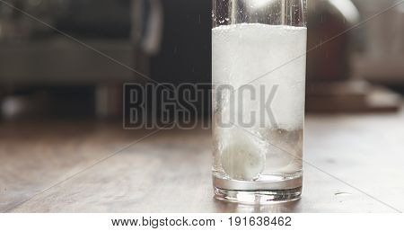 white effervescent tablet in glass with water on table, wide photo