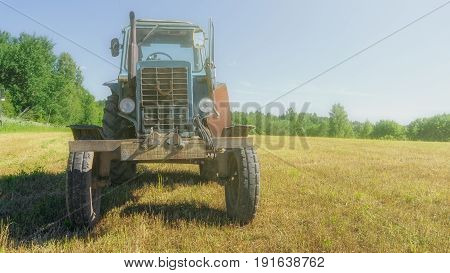 red old rusty tractor in a field of mown grass against a forest background in good weather