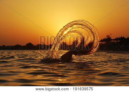 Beautiful young woman throwing back her hair into the water at the beach. Happy girl on the sea. Summer vacation concept