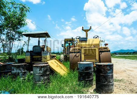 old yellow tractor parked with Old oil tank