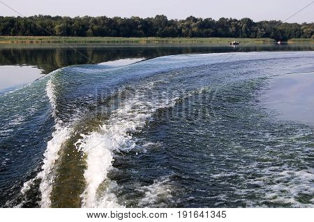 Fishtail Wave And Bank Of River Behind Inflatable Engine Boat