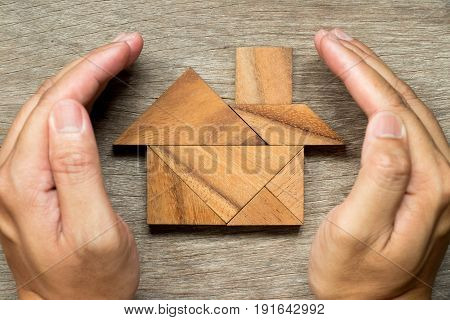 Hands hold the tangram puzzle in home shape (Concept for Home protection or insurance)
