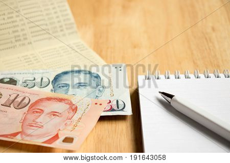 Bank passbook with Singapore dollar and book with pen on wood table background