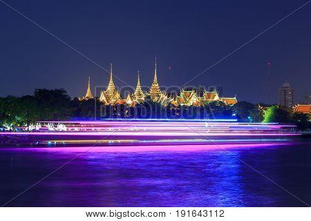 Bangkok , Thailand - 25  May, 2017 : wat phra kaew with blur light of boat moving passed