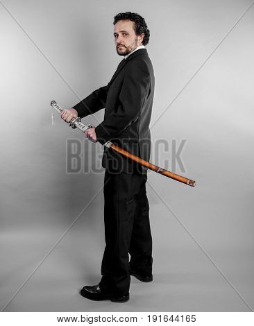 Security Businessman in black suit and armed japanese sword on gray background