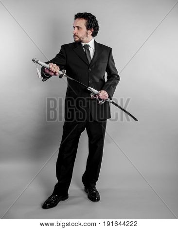 Defense Businessman in black suit and armed japanese sword on gray background