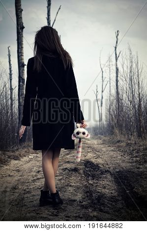 young girl walking on the road with toy in hand