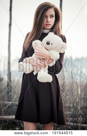 beautiful teenager girl with teddy bear toy in hands on background of burnt forest