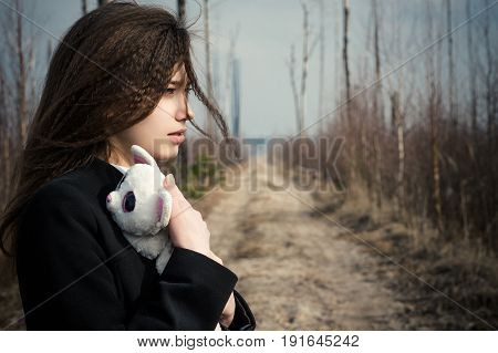 beautiful young girl hugging a toy on the background of burnt forest