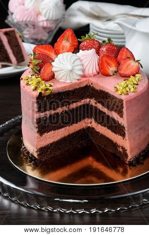 Chocolate strawberry cake decorated with berries meringue and pistachios in a cut